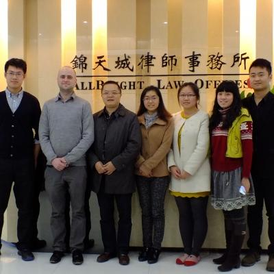 A group of Business Interns pose for a group photo infront of a reception desk at a law office in China.